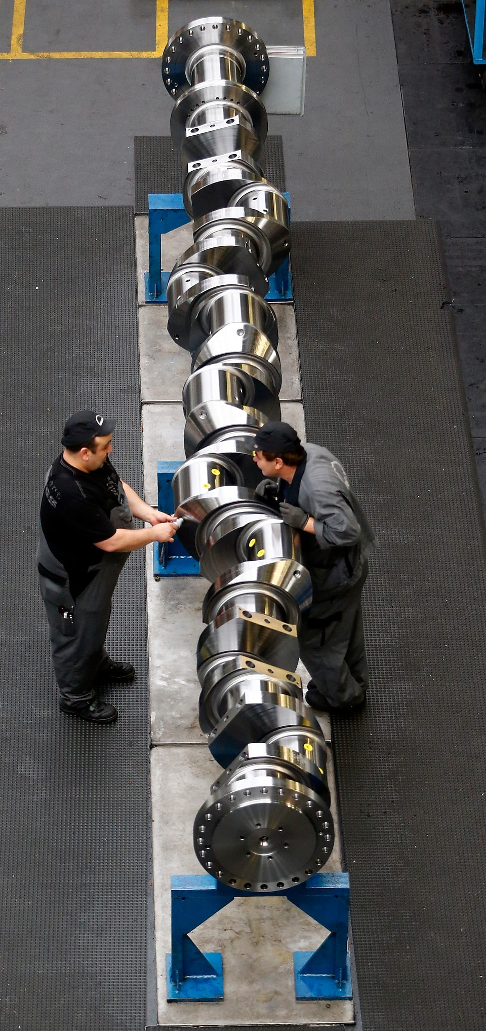 Workers assemble a part for a large Diesel engine at the MAN Diesel & Turbo factory