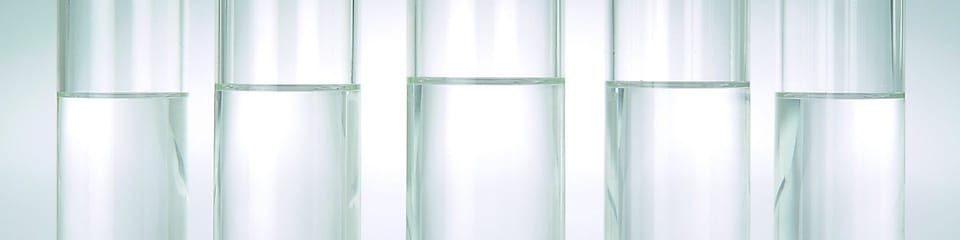 Five beakers in a row with a clear liquid in each one