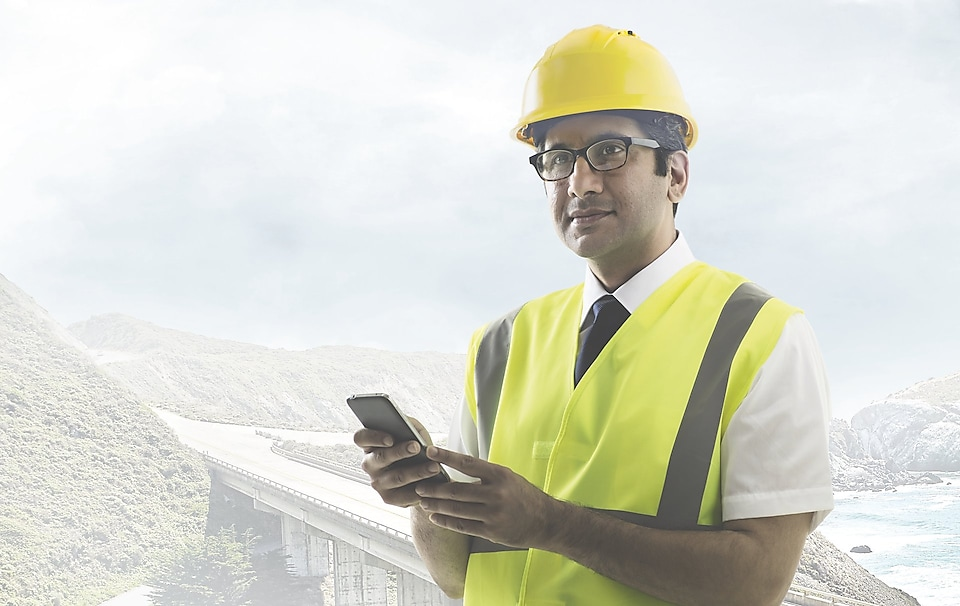 Man wearing a yellow safety helmet holding a phone