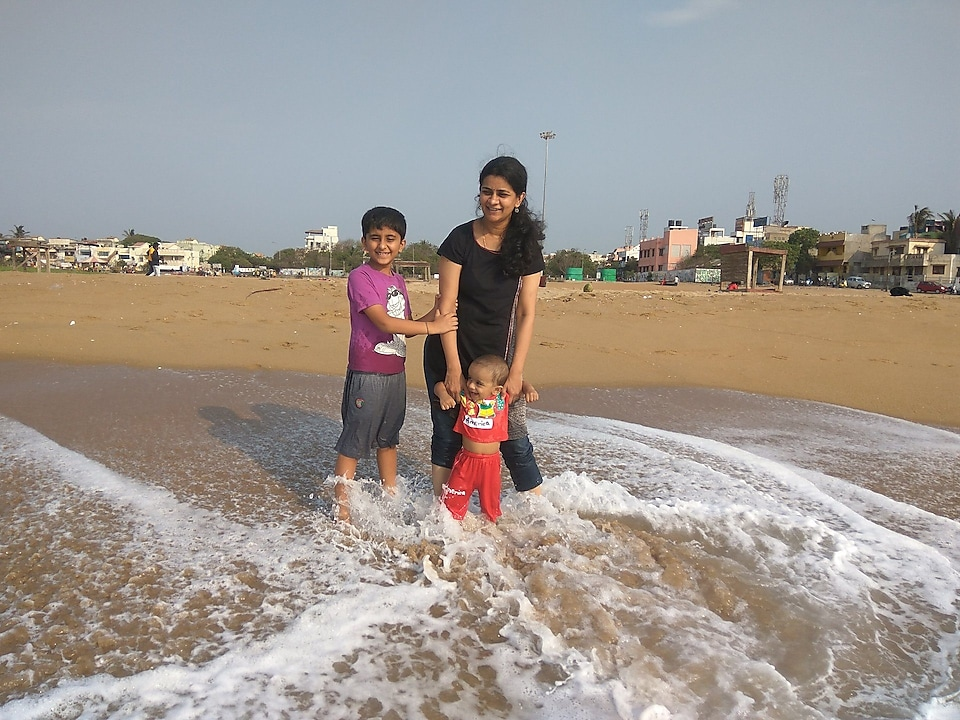 Swetha with her kids on a beach