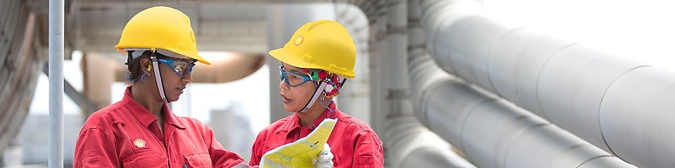 two workers discussing a project in a refinery in Malaysia