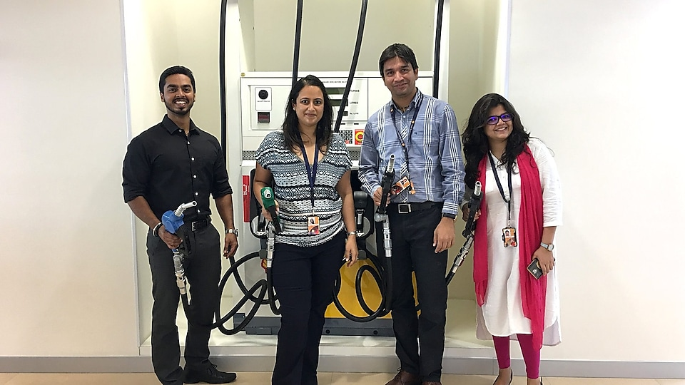 Yasmin and colleagues pose in front of a replica petrol pump