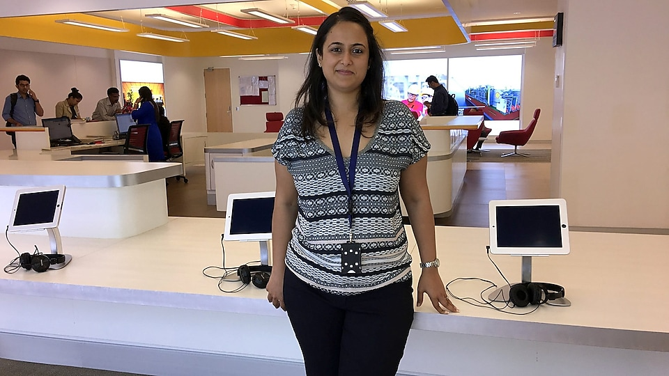 Yasmin stands in front of a reception desk