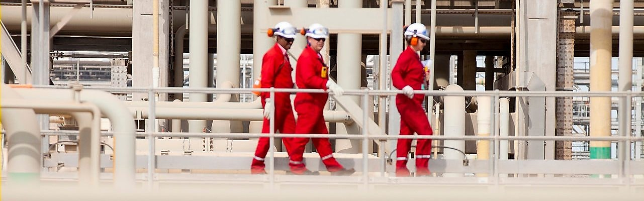 Shell workers walking across the pipe track