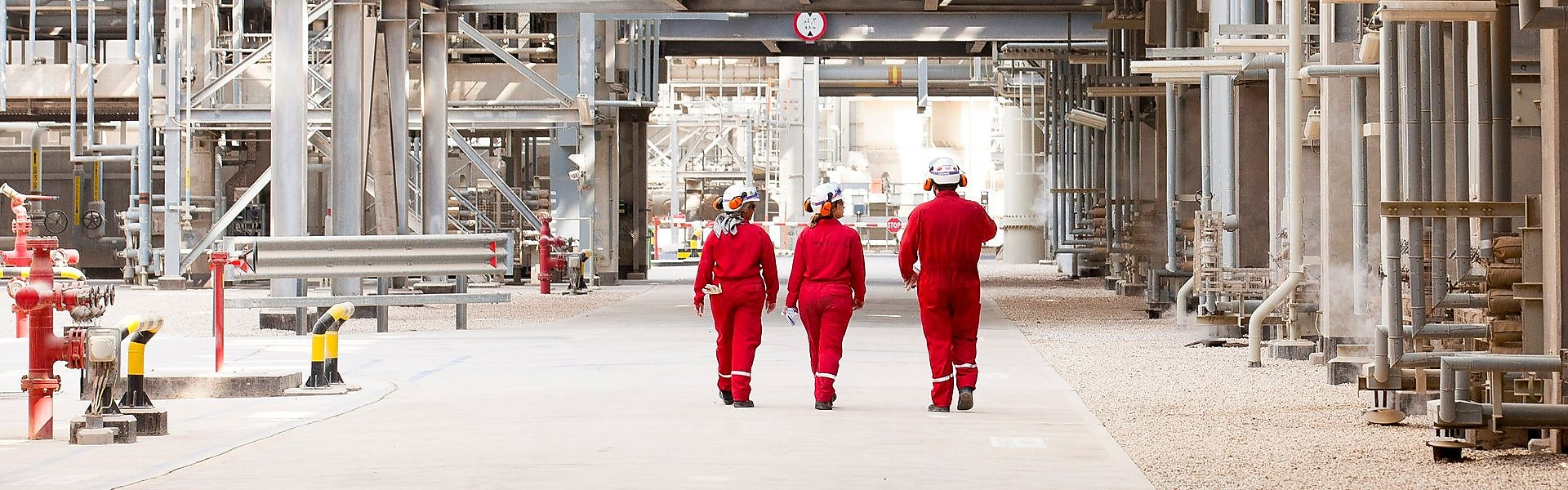 Three engineers walking on site through a refinery