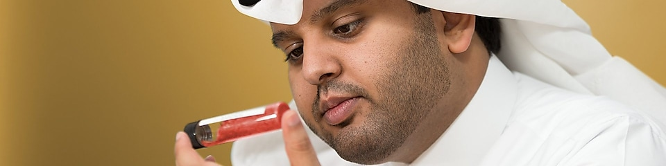 Mohammed Al Athba examines the contents of a capped test tube