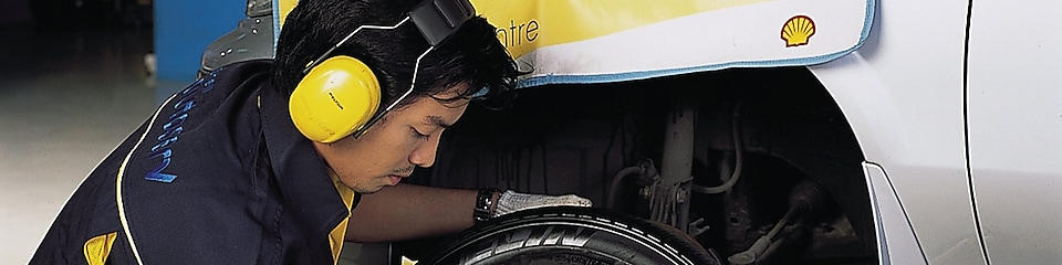 man changing front car tyre at workshop
