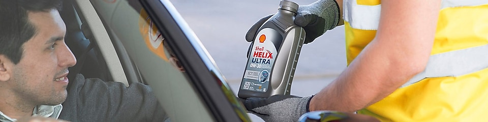 station attendant showing a bottle of shell helix ultra to a man in a car