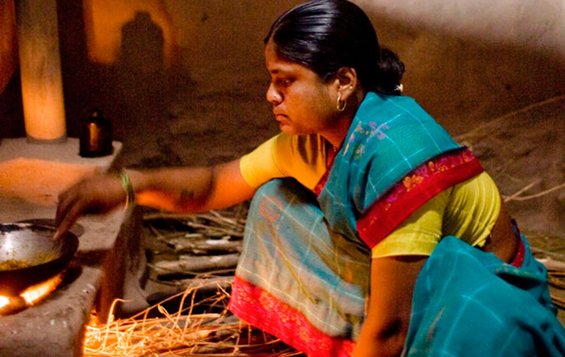 A woman cooks using traditional 'chulha'